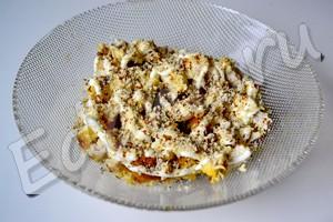 Выложите в салатник филе, смажьте майонезом, посыпьте орехами