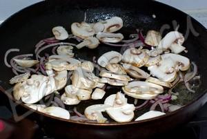 Добавьте к луку грибы, продолжайте жарить