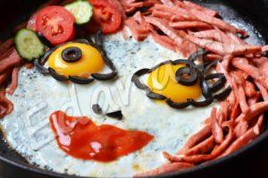 Украсьте глазунью овощами и кетчупом, чтобы получилась мордака